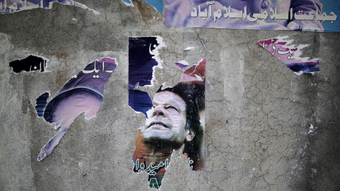 A defaced poster of former cricket star-turned-politician, and leader of Pakistan Tehreek-e-Insaf party, Imran Khan, is pasted on a wall in Islamabad, Pakistan, Friday, May 10, 2013. An especially violent spate of killings, kidnappings and bombings marred the run-up to Pakistan's nationwide election, capped Thursday by the abduction of the son of a former prime minister as he was rallying supporters on the last day of campaigning before the historic vote. (AP Photo/Muhammed Muheisen)