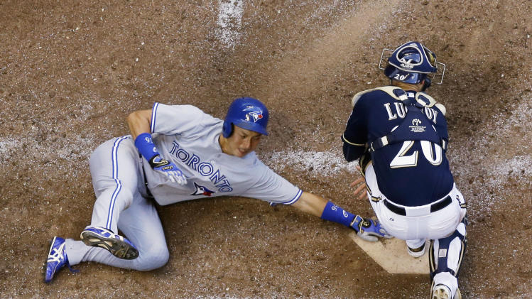 Milwaukee Brewers catcher Jonathan Lucroy can't handle the throw as Toronto Blue Jays' Munenori Kawasaki slides safely home during the sixth inning of a baseball game Wednesday, Aug. 20, 2014, in Milwaukee. Kawasaki scored from second on a hit by Jose Reyes. (AP Photo/Morry Gash)
