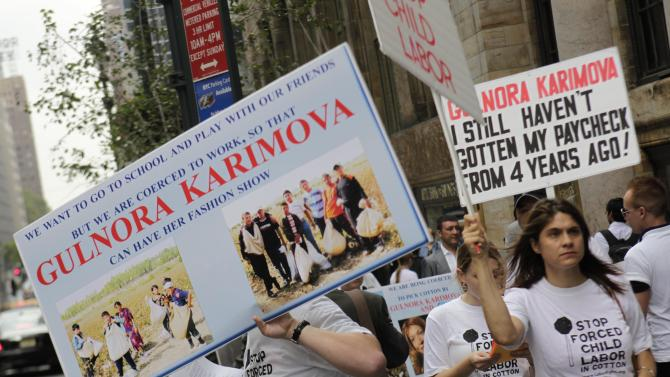 Protesters are seen before the start of the GULI fashion show in New York, Thursday, Sept. 15, 2011. Over the weekend, the producers of New York's Fashion Week canceled a show by designer Gulnara Karimova amid pressure from a human rights group and a planned protest over the use of child labor in her country. Karimova's backers revived the event Thursday at Cipriani on 42nd Street.    (AP Photo/Seth Wenig)