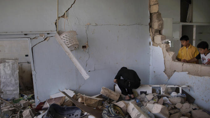 A Syrian man searches for belongings through the rubble of his house which was destroyed from a Syrian government forces shelling, in Azaz, on the outskirts of Aleppo, Syria, Wednesday, Aug. 29, 2012. (AP Photo/Muhammed Muheisen)