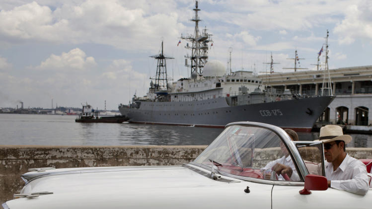 An American classic car drives past the Russian warship the Viktor Leonov CCB-175, docked in Havana's harbor in Havana, Cuba, Thursday, Feb. 27, 2014. The Russian warship that is one of the fleet's Vishnya-class ships which are generally used for intelligence gathering was docked in the harbor on Thursday, a day after the country's defense minister announced plans to expand Russia's worldwide military presence. (AP Photo/Franklin Reyes)