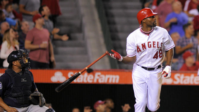 FILE - This Sept. 25, 2012 file photo shows Los Angeles Angels' Torii Hunter, right, dropping his bat as he hits a two-run home run as Seattle Mariners catcher Miguel Olivo looks on during the fifth inning of their baseball game against the Seattle Mariners  in Anaheim, Calif. A person with knowledge of the negotiations says free agent outfielder Hunter has agreed to a two-year deal with the Detroit Tigers. The person, who spoke Wednesday, Nov. 14, 2012, on condition of anonymity because no announcement has been made, says the deal is pending a physical. (AP Photo/Mark J. Terrill, File)