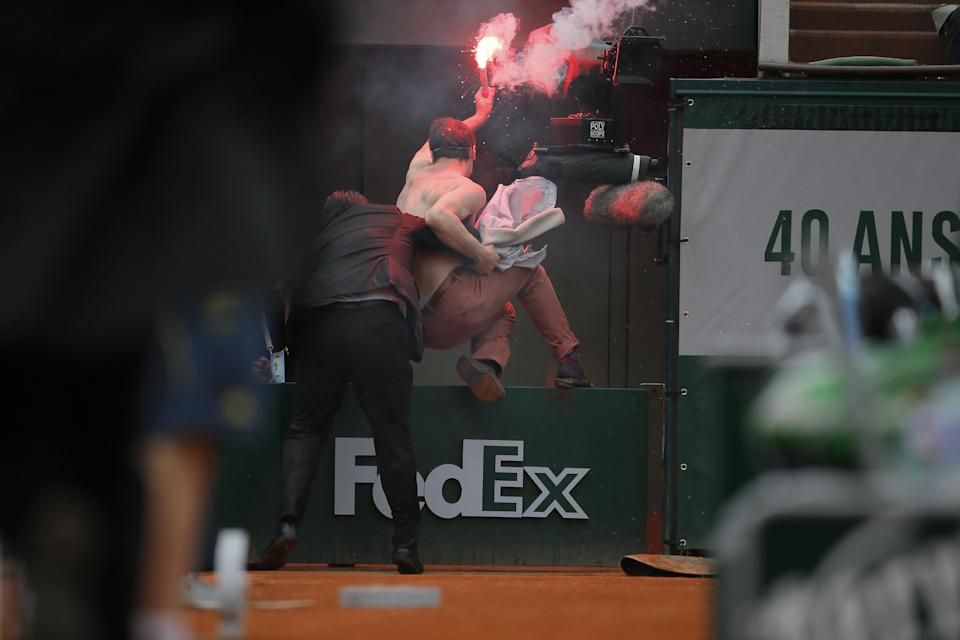 A security guard removes a demonstrator who ran onto center court as Spain's Rafael Nadal plays against compatriot David Ferrer in the final of the French Open tennis tournament, at Roland Garros stadium in Paris, Sunday June 9, 2013. (AP Photo/Michel Spingler)