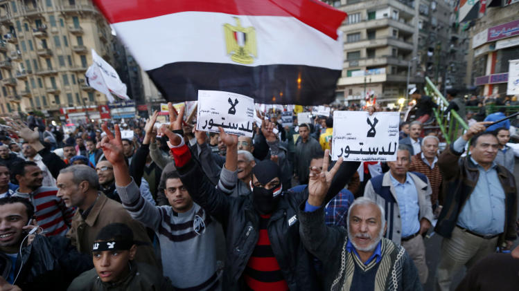 """Protesters chant slogans at during a demonstration against a constitution drafted by Islamist supporters of President Mohammed Morsi in Tahrir square in Cairo, Egypt, Friday, Dec. 14, 2012. Opposing sides in Egypt's political crisis were staging rival rallies on Friday, the final day before voting starts on a contentious draft constitution that has plunged the country into turmoil and deeply divided the nation. The placards in Arabic read, """"no for the constitution.""""(AP Photo/Petr David Josek)"""