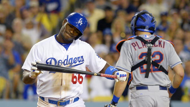 Los Angeles Dodgers' Yasiel Puig, left, reacts after striking out as New York Mets catcher Kevin Plawecki walks away during the sixth inning of a baseball game, Friday, July 3, 2015, in Los Angeles. (AP Photo/Mark J. Terrill)