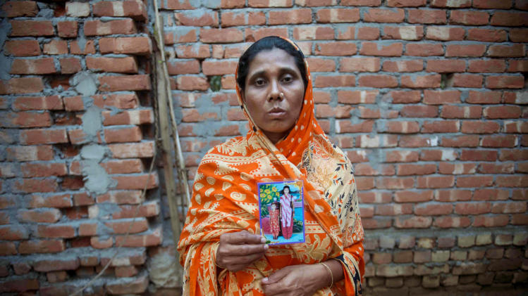 """In this photo taken Tuesday, May 21, 2013, Hawa Begum holds a photograph of her two daughters outside the family home in Tekani village in far northwestern Bangladesh. She and her eldest daughter, 18-year-old Moushimi, were working inside the Tazreen garment factory near Dhaka when it caught fire last November. Hawa escaped by jumping out of a window on the fifth floor. Moushimi, trapped behind the factory's locked gates, was killed along with 111 others. """"I pray every day for my daughter and for Allah saving me,"""" Hawa said. (AP Photo/Ismail Ferdous)"""