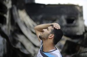A Palestinian looks at his family's food factory, which witnesses said was shelled and torched by the Israeli army during the offensive, in Deri al Balah in central Gaza Strip