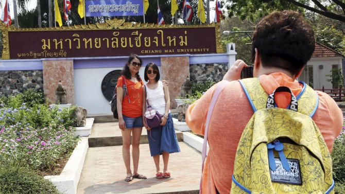 """In this March 30, 2014 photo, Chinese tourists pose for a photograph at the main entrance to Chiang Mai University in Chiang Mai province, northern Thailand. The bucolic, once laid-back campus of one of Thailand's top universities is under a security clampdown. Not against a terrorist threat, but against Chinese tourists. Thousands have clambered aboard student buses at the university, made a mess in cafeterias and sneaked into classes to attend lectures. Someone even pitched a tent by a picturesque lake. The reason: """"Lost in Thailand,"""" 2012 slapstick comedy partly shot on campus that is China's highest-grossing homegrown movie ever. (AP Photo/Apichart Weerawong)"""