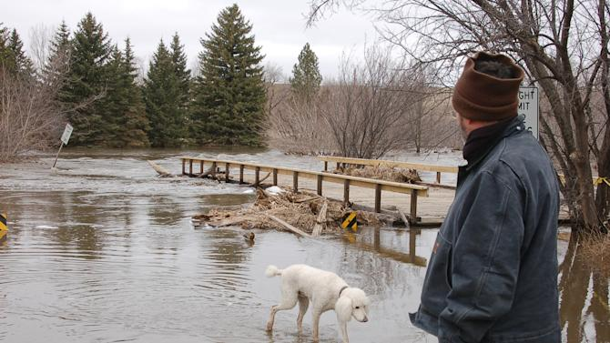 Robert Kibler and his dog, Alfie, survey the flooded Des Lacs River in Burlington, N.D., on Wednesday, April 13, 2011. Kibler and his wife, Alex Duefel, left their home on Tuesday but returned Wednesday to move their collection of 7,000 books to a main floor. (AP Photo/James MacPherson)