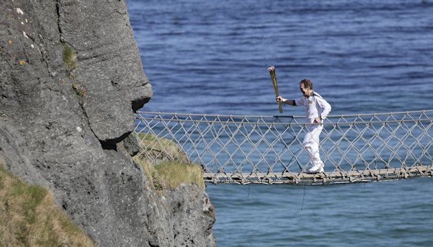 Denis Broderick carries the Olympic Torch over the Carrick-a-Rede rope bridge in county Antrim, Northern Ireland, Monday, June 4, 2012.  The Olympic Torch is continuing its relay journey around the co