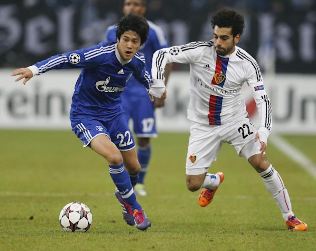 Schalke's Atsuto Uchida, left, and Basel's Mohamed Salah challenge for the ball during the Champions League group E soccer match between FC Schalke 04 and FC Basel in Gelsenkirchen, Germany, W
