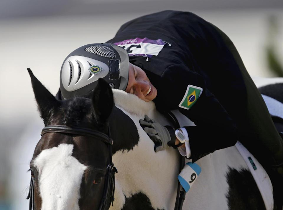 Yane Marques, of Brazil, pats her horse Over The Odds after completing the course in the equestrian show jumping stage of the women's modern pentathlon at the 2012 Summer Olympics, Sunday, Aug. 12, 2012, in London. (AP Photo/David Goldman)