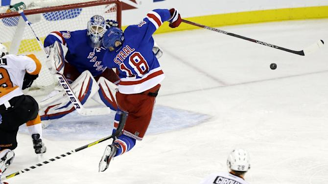 New York Rangers' Marc Staal (18) reacts after being hit by a puck during the third period of an NHL hockey game against the Philadelphia Flyers on Tuesday, March 5, 2013, in New York. Rangers goalie Henrik Lundqvist, of Sweden, watches. The Rangers won the game 4-2. (AP Photo/Frank Franklin II)