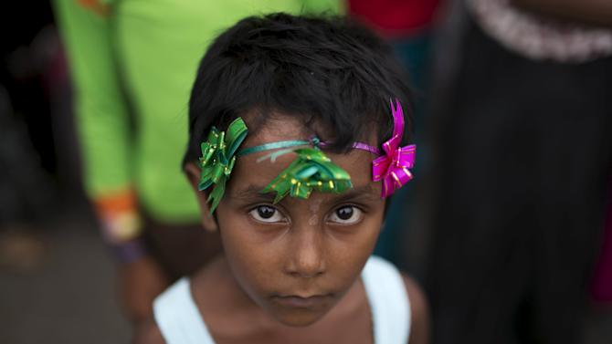 A young Rohingya migrant who arrived in Indonesia this week by boat waits for a medical check up at a temporary shelter for refugees in Aceh Timur regency, near Langsa in Indonesia's Aceh Province
