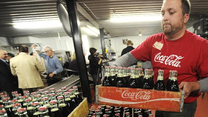 FILE - Adam Peterson stakes crates of the last run of 6.5-ounce returnable glass bottles Tuesday, Oct. 9, 2012, at the Coca-Cola Bottling Company in Winona, Minn. The small Coke bottler in Minnesota says it's stopping production of the bottles, which customers could return to get back a 20-cent deposit. The company in Winona, Minn., had been refilling the returnable bottles since 1932 but said it no longer makes business sense to continue doing so. (AP Photo/Winona Daily News, Andrew Link)