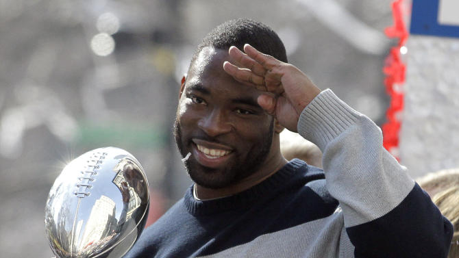 New York Giants defensive end Justin Tuck salutes while holding the Vince Lombardi trophy during a ticker-tape parade celebrating the team's NFL Super Bowl XLVI championship, Tuesday, Feb. 7, 2012, in New York. The Giants beat the New England Patriots 21-17 on Sunday in Indianapolis. (AP Photo/Julio Cortez)