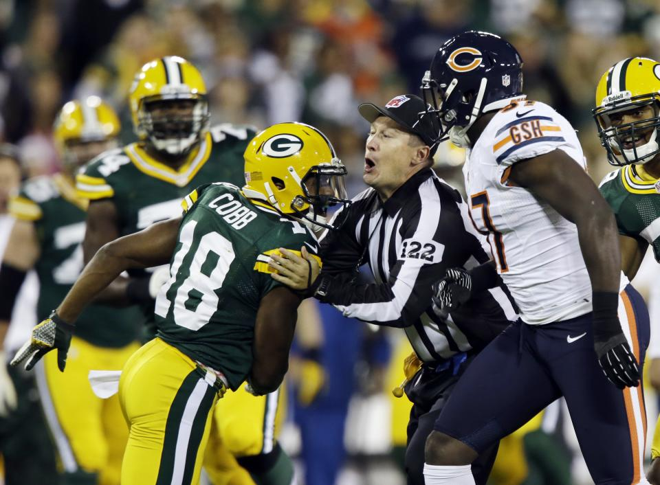 Field judge George Trout gets between Green Bay Packers' Randall Cobb (18) and Chicago Bears' J.T. Thomas (97) during the first half of an NFL football game Thursday, Sept. 13, 2012, in Green Bay, Wis. (AP Photo/Jeffrey Phelps)