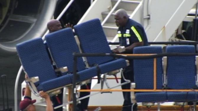 "In this photo provided by WBZ-TV seats from an American Airlines 757 are carried before receiving ""Main Cabin Extra Refurbishment"" Tuesday, Oct. 2, 2012, at Logan International Airport in Boston. American Airlines says passenger seats on a third flight came loose as the plane was airborne Tuesday, and it's continuing to inspect other jets with similar seating. The airline acknowledged Tuesday that seats came loose on a flight last week from Dallas-Fort Worth International Airport to Vail, Colo., and the same thing happened aboard the same plane Monday and a second plane Saturday, according to the airline. (AP Photo/WBZ-TV) MANDATORY CREDIT"
