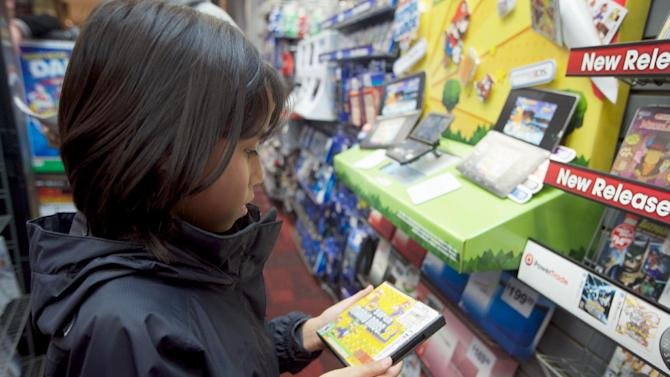 IMAGE DISTRIBUTED FOR NINTENDO - Joanna Reyes, 10, of Seattle searches the shelves at the GameStop Southcenter store in Seattle in pursuit of New Super Mario Bros. 2, a must-have Nintendo 3DS game, during a Black Friday shopping trip on Friday, Nov. 23, 2012. (Photo by Stephen Brashear/Invision for Nintendo/AP Images)