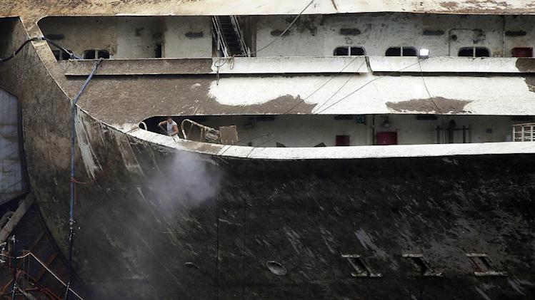 A worker sprays water on a deck of the luxury cruise ship Costa Concordia as the vessel is refloated and almost ready to be towed away from the tiny Tuscan island of Isola del Giglio, Italy, early Tuesday, July 22, 2014. The wreck of the Costa Concordia is expected to be towed to the Italian port of Genoa on Wednesday, where it will be scrapped. 32 people died when it slammed into the reef and started capsizing. The body of one victim is still missing. (AP Photo/Gregorio Borgia)