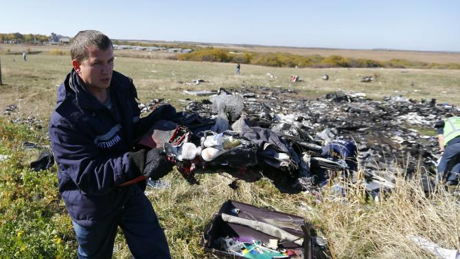 An Emergencies Ministry member walks near belongings and wreckage at the site where the downed Malaysia Airlines flight MH17 crashed, in Donetsk region