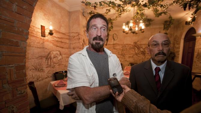 "Software company founder John McAfee, left, accompanied by his lawyer Telesforo Guerra, right, answers questions during an interview at a local restaurant in Guatemala City, Tuesday, Dec. 4, 2012.  McAfee, 67, has been identified as a ""person of interest"" in the killing of his neighbor in Belize, 52-year-old Gregory Faull. Police are urging McAffe to come in for questioning. The anti-virus company founder fled Belize and is seeking political asylum in Guatemala, according to his lawyer Telesforo Guerra. (AP Photo/Moises Castillo)"