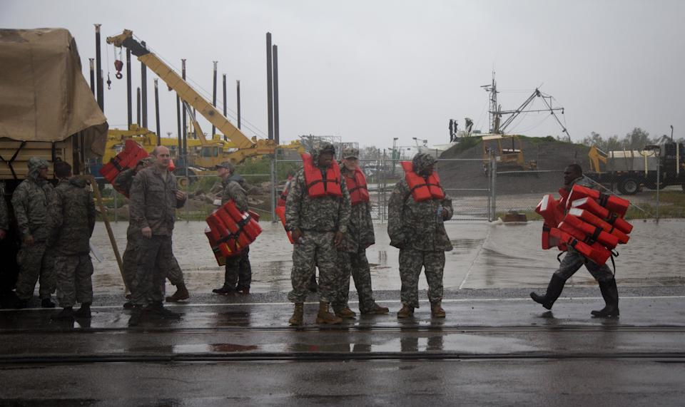 Guardsmen distribute life vests near Braithwaite, La., as they prepare to help flood victims from Plaquemines Parish, a rural area outside New Orleans that was flooded during Hurricane Isaac on Wednesday, Aug. 29, 2012. (AP Photo/Erik Schelzig)
