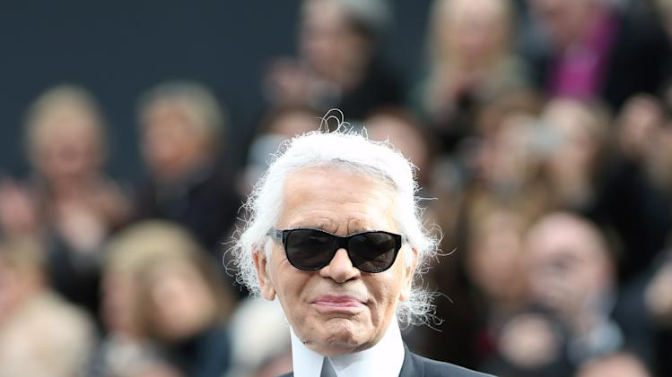 German fashion designer Karl Lagerfeld acknowledges applause at the end of Chanel's Fall/Winter 2013-2014 ready to wear collection, in Paris, Tuesday, March, 5, 2013. (AP Photo/Thibault Camus)