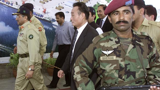 FILE - In this Friday, March 21, 2002 file photo, Pakistani President Gen. Pervez Musharraf, left, with Chinese Vice Premier Wu Bangguo, center, leaves the port under tight security after a ground breaking ceremony of Gwadar Port Project, 700 kilometers (435 miles) from Karachi, Pakistan. China is poised to take over operational control of Gwadar port, a strategic, deep-water port on Pakistan's southwestern coast that could serve as a vital economic hub for Beijing and potentially a key military outpost. (AP Photo/B.K. Bangash, file)