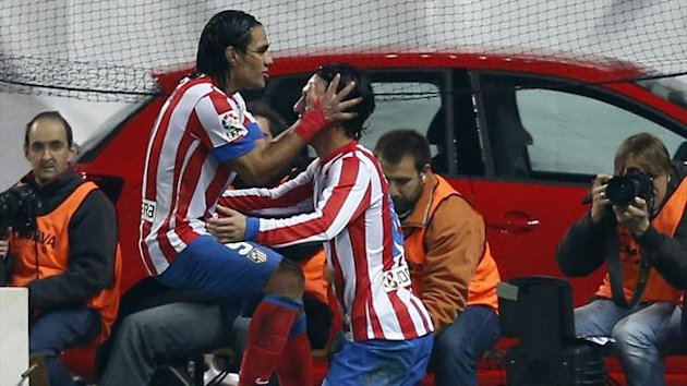Atletico Madrid's Radamel Falcao (L) congratulates his team mate Arda Turam after scoring a goal against Sevilla during their Spanish first division soccer match at Vicente Calderon stadium (Reuters)