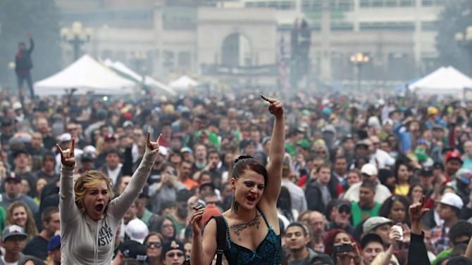 FILE - In this April 20, 2013 file photo, members of a crowd numbering tens of thousands smoke marijuana and listen to live music, at the Denver 420 pro-marijuana rally at Civic Center Park in Denver. Medical marijuana businesses worried that federal agents will close them down now have a roadmap to avoid prosecution, courtesy of the Justice Department's decision to allow legal pot in Colorado and Washington state.(AP Photo/Brennan Linsley, File)