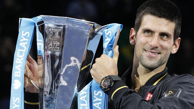 Novak Djokovic of Serbia holds up the ATP World Tour Tennis singles trophy as he poses for photographers after defeating Roger Federer of Switzerland after the final in London, Monday, Nov. 12, 2012. (AP Photo/Sang Tan)