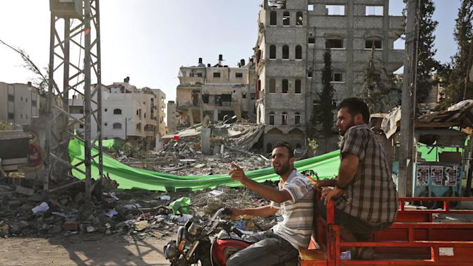 Palestinians drive past a building destroyed by an Israeli strike on Friday, in Gaza City, Sunday, July 13, 2014. Thousands of Palestinian residents of the northern Gaza Strip fled their homes on Sunday and sought safety in U.N. shelters, heeding warnings from the Israeli military about impending plans to bomb the area in the sixth day of an offensive against Hamas that has killed more than 160 people. (AP Photo/Lefteris Pitarakis)