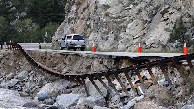 A guardrail hangs away from a closed canyon road, where some local residents are allowed to drive with caution, and which is washed out in places by recent flooding, up Boulder Canyon, west of Boulder, Colo., Friday Sept. 20, 2013. With snow already dusting Colorado's highest peaks, the state is scrambling to replace key mountain highways washed away by flooding. More than 200 miles of state highways and at least 50 bridges were damaged or destroyed, not counting many more county roads. (AP Photo/Brennan Linsley)