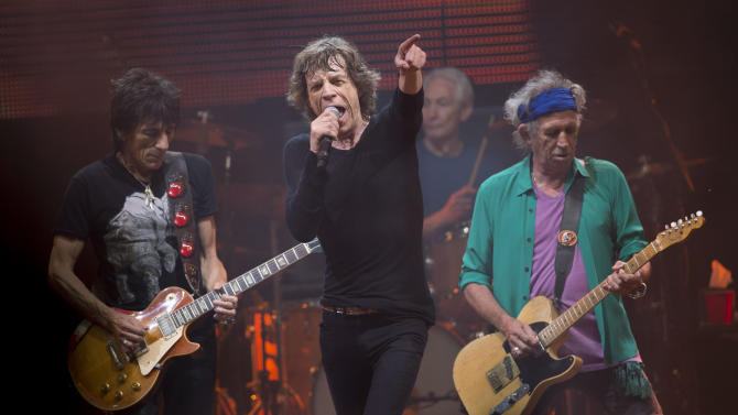 Mick Jagger, center, Ronnie Wood, left ,Charlie Watts, rear on drums and Keith Richards, right, of British band the Rolling Stones, perform on the Pyramid main stage at Glastonbury, England, Saturday, June 29, 2013. Thousands of music fans have arrived for the festival to see headliners, Arctic Monkeys, Mumford and Sons and the Rolling Stones.(Photo by Joel Ryan/Invision/AP)