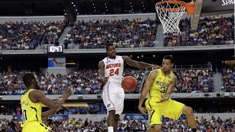 Michigan's Trey Burke (3) passes the ball to Tim Hardaway Jr. (10) in front of Florida's Casey Prather (24) during the second half of a regional final game in the NCAA college basketball tournament, Sunday, March 31, 2013, in Arlington, Texas. (AP Photo/David J. Phillip)