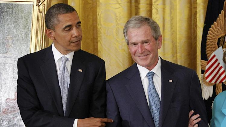 President Barack Obama points to former President George W. Bush during a ceremony to unveil his official portrait, Thursday, May 31, 2012, in the East Room at the White House in Washington. (AP Photo/Charles Dharapak)