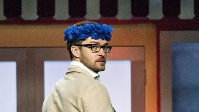 Entertainer Justin Timberlake, dressed in a grass skirt, poses for the audience during the Walmart shareholders' meeting in Fayetteville, Ark., Friday, June 1, 2012. Timberlake hosted the annual event. (AP Photo/April L. Brown)
