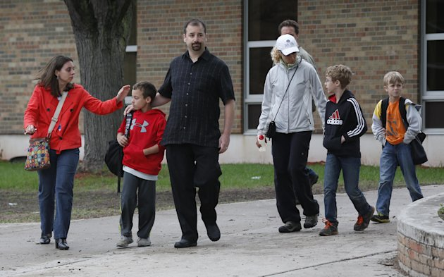 Parents and their children leave the Peter Hobart Elementary School in St. Louis Park, Minn., after a field trip to Lilydale Regional Park resulted in the death of at least one student Wednesday, May