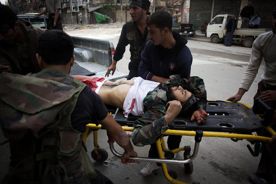 A gravely wounded Free Syrian Army fighter is helped by his comrades at the entrance to Dar El Shifa hospital in Aleppo, Syria, Sunday, Oct. 21, 2012. (AP Photo/Manu Brabo)
