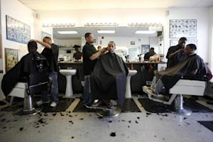 Dorsey Jackson, center standing, cuts hair at his establishment …