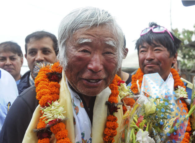 80-year-old Japanese climber Yuichiro Miura, who became the oldest conqueror of Mount Everest on Thursday, is garlanded as he returns from camp 2 by helicopter in Katmandu, Nepal, Sunday, May 26, 2013