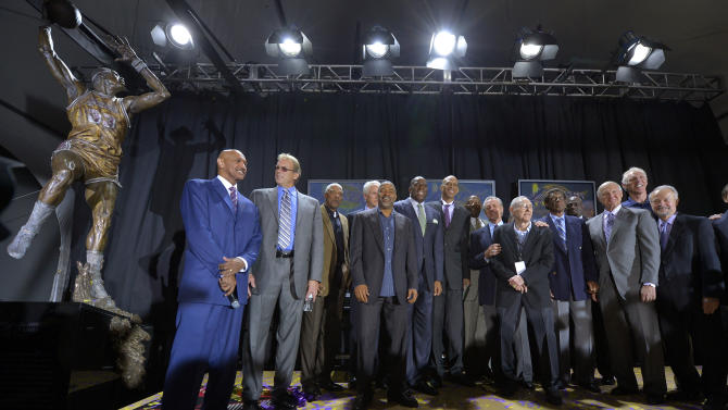Guests pose with former Los Angeles Lakers center Kareem Abdul-Jabbar, center, after unveiling his statue in front of Staples Center, Friday, Nov. 16, 2012, in Los Angeles. (AP Photo/Mark J. Terrill)