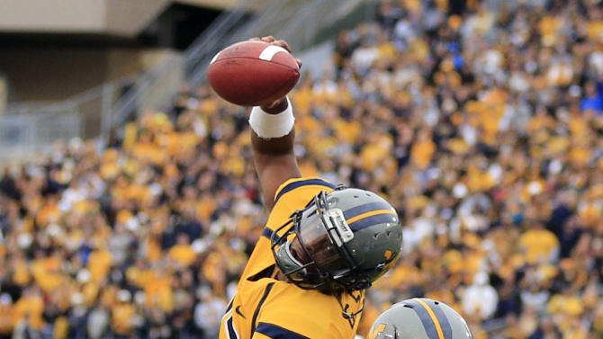 West Virginia quarterback Geno Smith (12) is tackled at the goal line by TCU's Kevin White (25) and Joel Hasley (36) during the first half of their NCAA college football game in Morgantown, W.Va., on Saturday, Nov. 3, 2012. (AP Photo/Christopher Jackson)