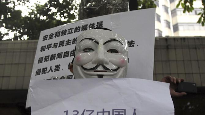 """A supporter of Southern Weekly newspaper wears a Guy Fawkes mask while protesting with a banner that reads """"1.3 billion Chinese have rights to their own voice and do not want to be represented'' outside the newspaper's headquarters in Guangzhou in south China's Guangdong province Tuesday Jan. 8, 2013.  Free-speech protesters in masks squared off against flag-waving communist loyalists in a southern Chinese city Tuesday as a dispute over censorship at a newspaper spilled into the broader population, with authorities shutting microblog accounts of supporters of the paper. (AP Photo) CHINA OUT"""