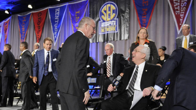 ESPN President John Skipper, left, and Southeastern Conference Commissioner Mike Slive chat as they and a collection of SEC coaches finish a news conference announcing the launching of the SEC Network in partnership with ESPN, held Thursday, May 2, 2013, in Atlanta. The network will produce 1,000 live events each year, including 450 televised on the network and 550 distributed digitally. (AP Photo/John Amis)
