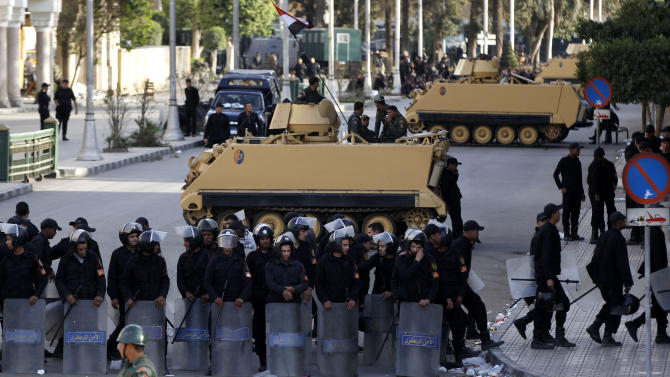 Egyptian riot police stand guard in front of the presidential palace in Cairo, Egypt, Tuesday, Dec. 11, 2012. Thousands of opponents and supporters of Egypt's Islamist president were flocking to key locations in the nation's capital ahead of rival mass rallies Tuesday, four days before a nationwide referendum on a contentious draft constitution.  (AP Photo/Petr David Josek)