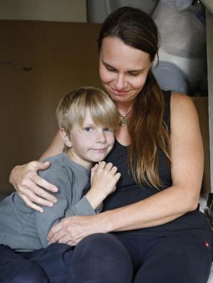 Jessica Klauzer-Zimmerman sits with her youngest son Liam, 8, in her flood damaged home in Boulder, Colo., on Wednesday, Sept. 18, 2013. Klauzer-Zimmerman woke up Thursday Sept. 12, to knee-deep water inside her townhouse, and has since been dealing with a maze of phone calls with insurance agents. Klauzer-Zimmerman said that each agent told her that her policy does not cover flood damage. Thousands of people who do not have flood insurance could face staggering costs to rebuild after the devastating floods in Colorado.(AP Photo/Ed Andrieski)