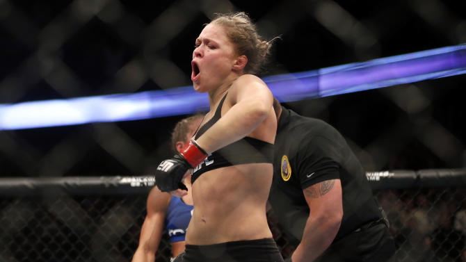 Ronda Rousey celebrates defeating Liz Carmouche after their UFC 157 women's bantamweight championship mixed martial arts match in Anaheim, Calif., Saturday, Feb. 23, 2013. Rousey won the first women's bout in UFC history, forcing Carmouche to tap out in the first round. (AP Photo/Jae C. Hong)