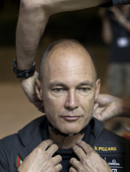 Solar Impulse pilot Bertrand Piccard is helped to fit his flying suit at Barajas airport in Madrid, Spain, Tuesday, June 5, 2012. The experimental solar-powered airplane arrived in Madrid on May 25, 2012 from Payerne, Switzerland, and now goes on to Rabat, Morocco on its first transcontinental trip. The mission is described as the final dress rehearsal for a round-the-world flight with a new and improved aircraft in 2014. (AP Photo/Alberto Di Lolli)